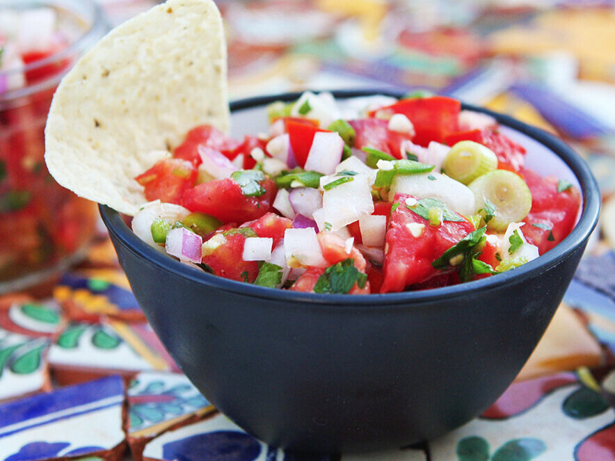 Bowl of spicy fresh salsa with jar of salsa next to it