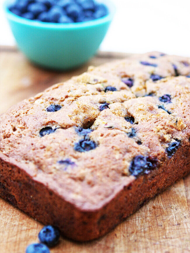 Loaf of blueberry zucchini bread sitting next to bowl of blueberries