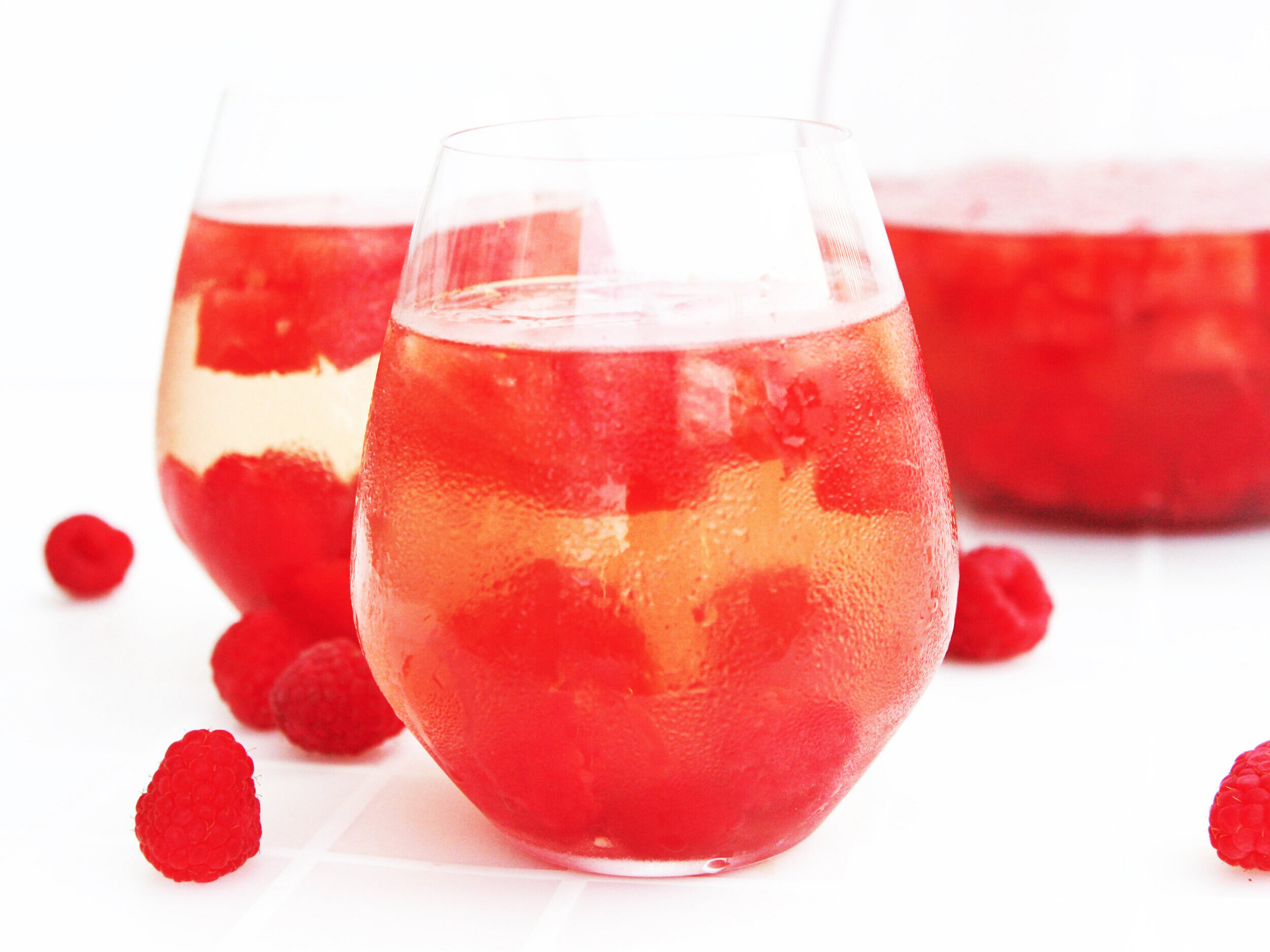 two glasses of raspberry sangria with raspberries inside
