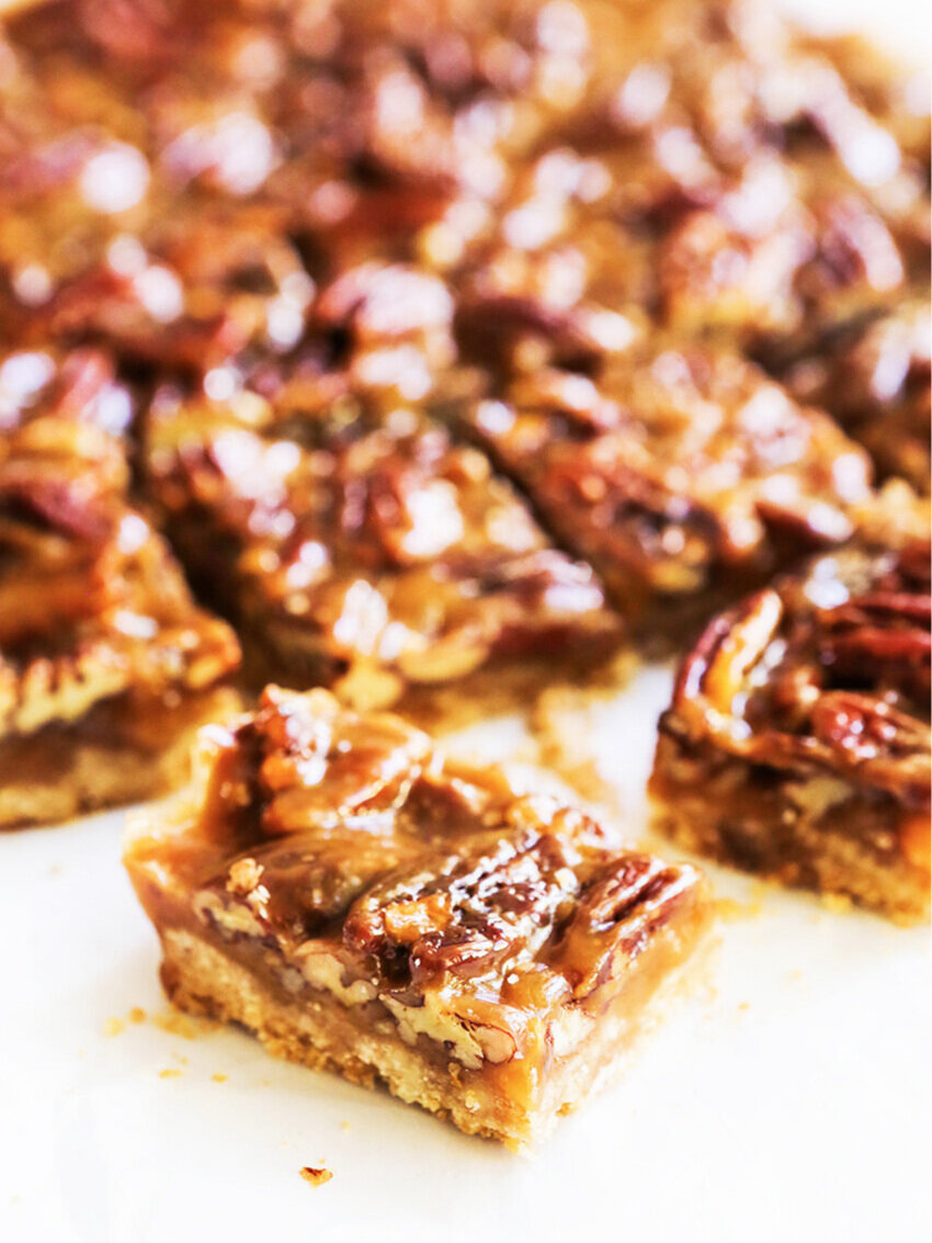 close up of caramel pecan bars with the pan in background