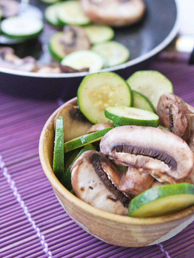 mushrooms and zucchini in a small bowl sitting next to pan