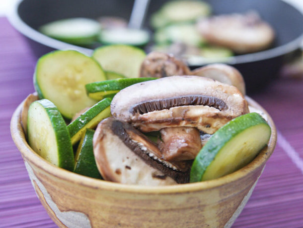 close up of bowl of mushrooms and zucchini on purple placemat