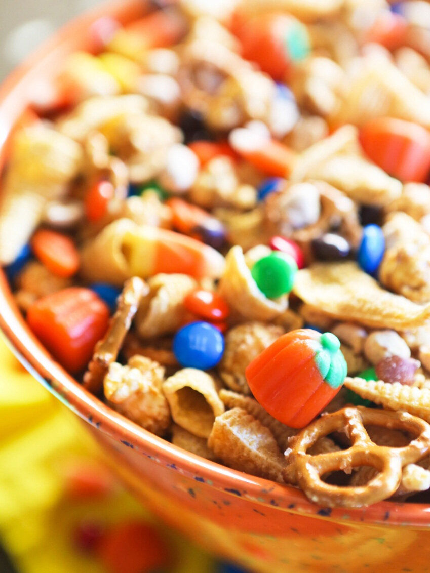 Side view of bowl of halloween snack mix with focus on candy pumpkin