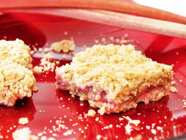 Rhubarb crunch bars sitting on red plate with rhubarb stalks