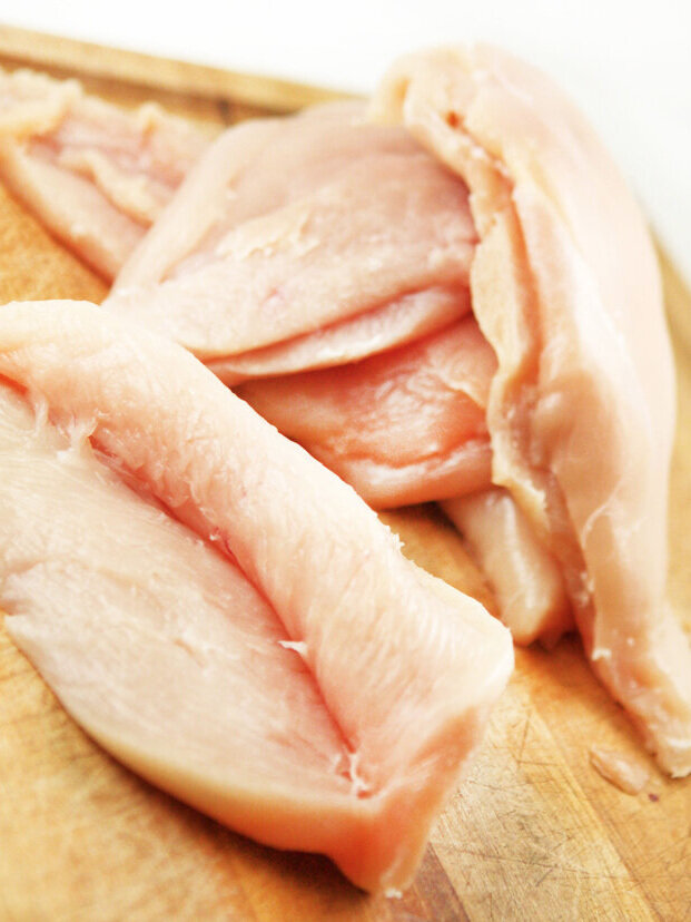 Chicken breasts with slits cut into them ready for stuffing