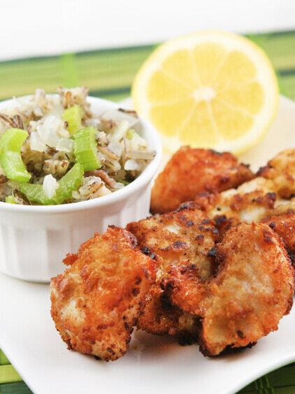 Fried walleye on a plate next to wild rice salad
