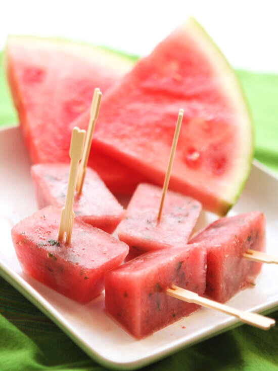 Watermelon ice cube popsicles on plate next to watermelon slices