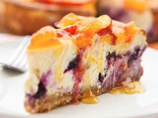 close up slice of blueberry cheesecake with peaches on top