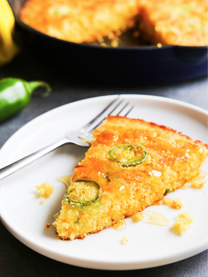 Slice of cornbread with jalapenos with skillet in background