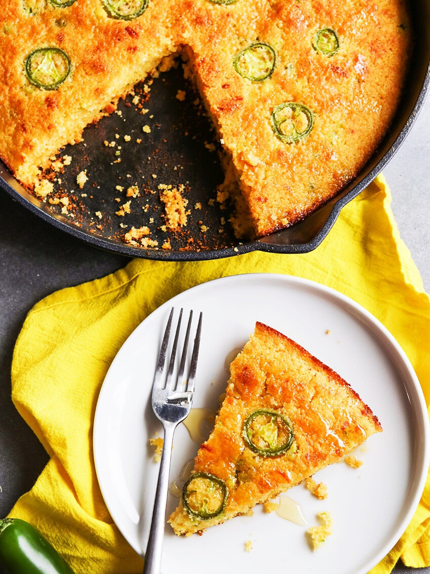 top view of skillet of cornbread next to plate with a slice of it