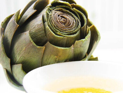 Cooked artichoke sitting next to bowl of melted butter
