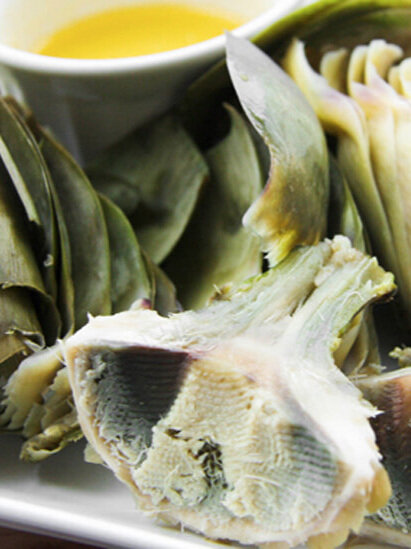 Artichoke heart surrounded by leaves and small bowl of melted butter