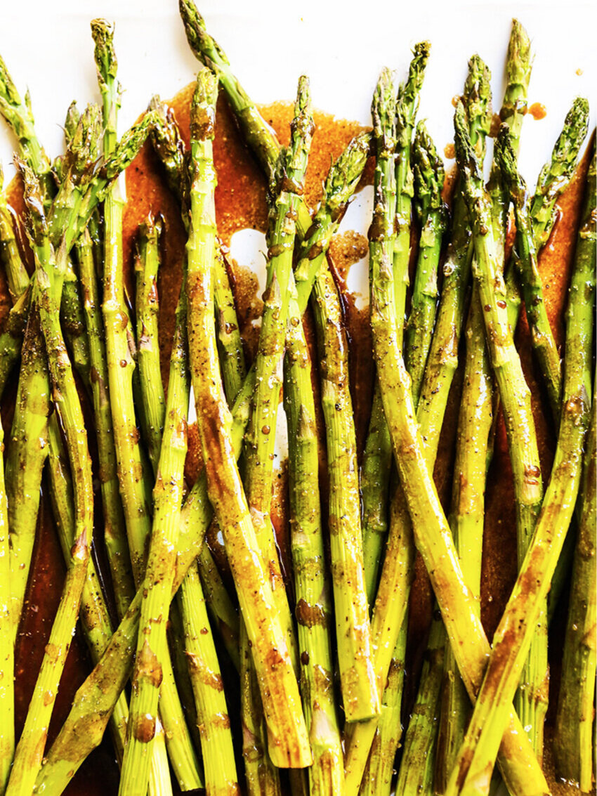top view of baked asparagus spears stacked with glazed drizzled over