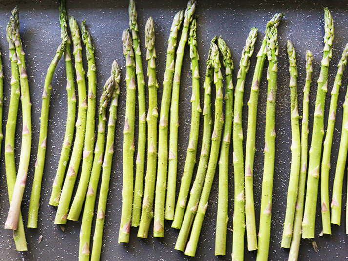 Asparagus spears in a single layer on baking sheet with salt and pepper