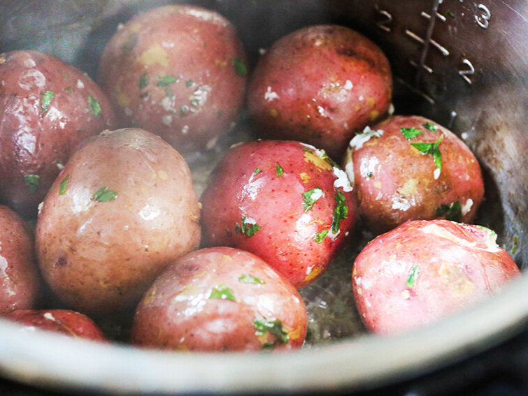 Red potatoes coated with garlic sauce in Instant Pot