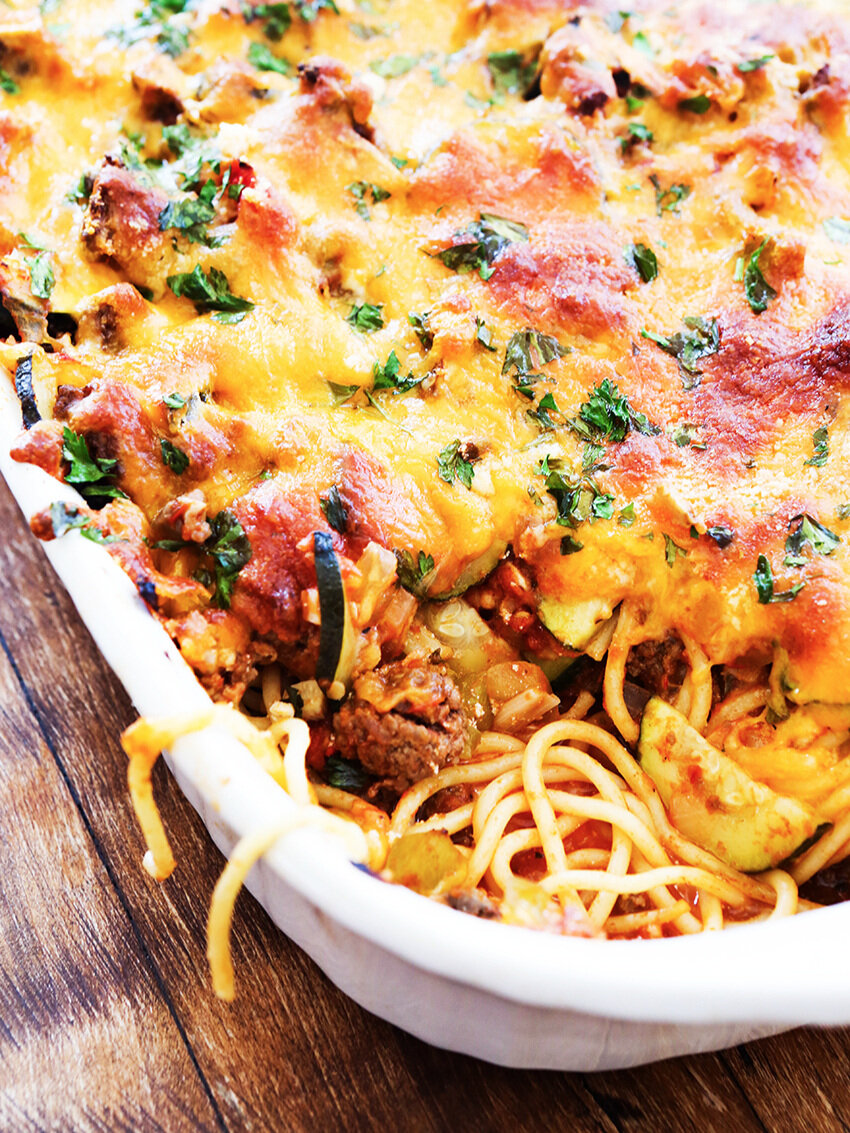 Baked Spaghetti in baking dish with spaghetti noodles hanging over side
