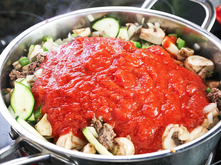 sauce over meat and veggies in skillet on stove top
