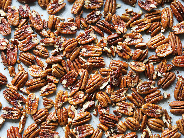 top view of baking sheet filled with uncooked pecans in single layer