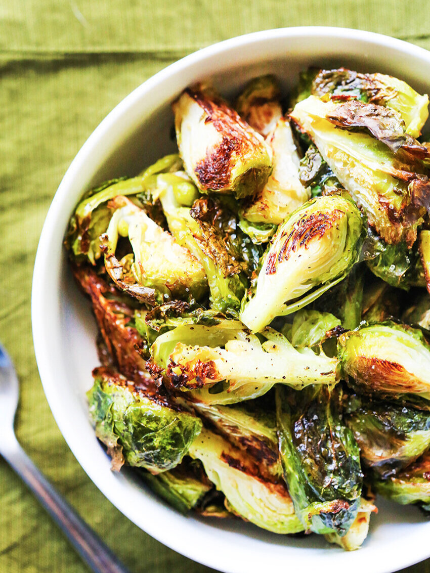 top view of bowl of roasted brussels sprouts with spoon next to it