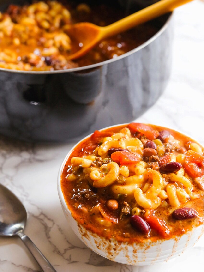 bowl of chili mac sitting next to pan filled with it
