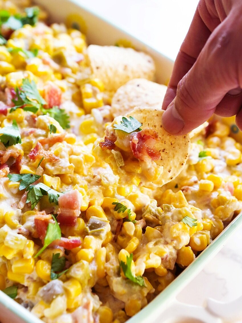 Hand with tortilla chip scooping corn dip out of baking dish
