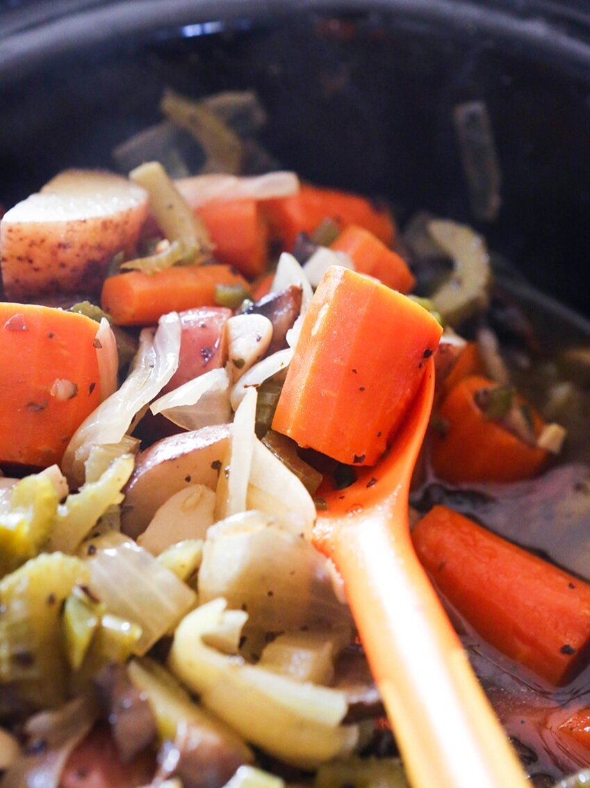Crock pot full of cooked veggies with serving spoon