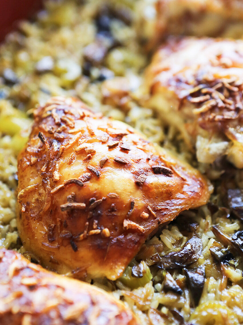 Close up of baked chicken thigh on a bed of rice