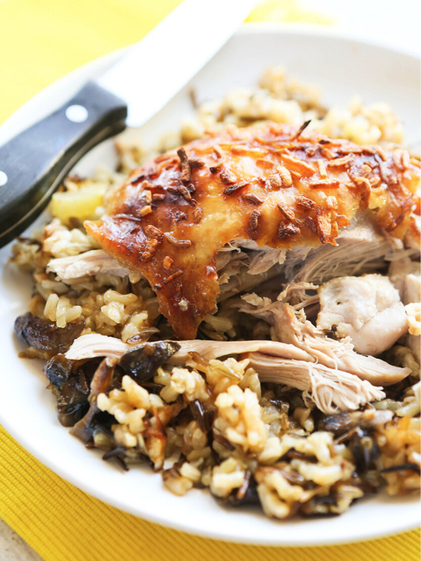 baked chicken thigh over rice with meat falling out and knife on plate
