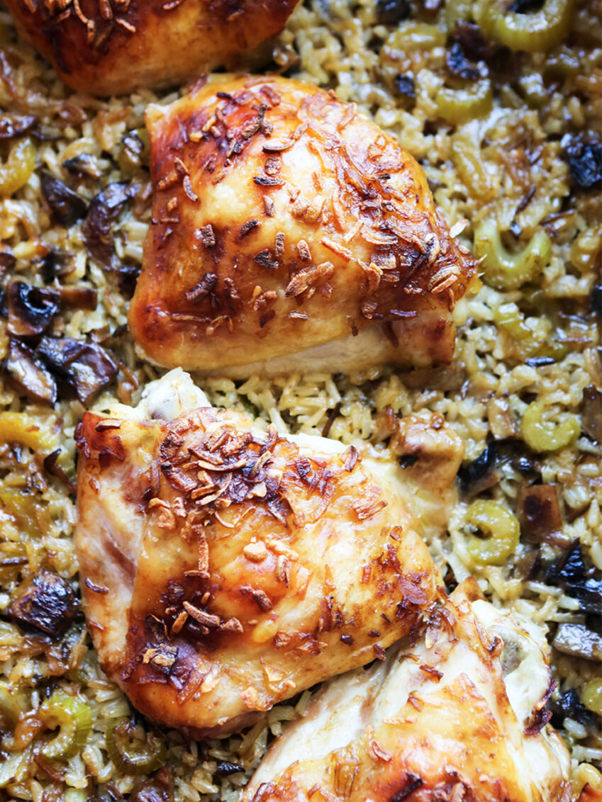 top view of baked chicken thighs on top of rice in pan