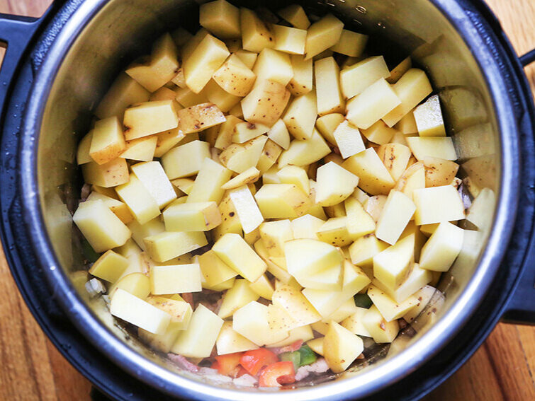 Potato pieces over veggies in Instant Pot ready to cook