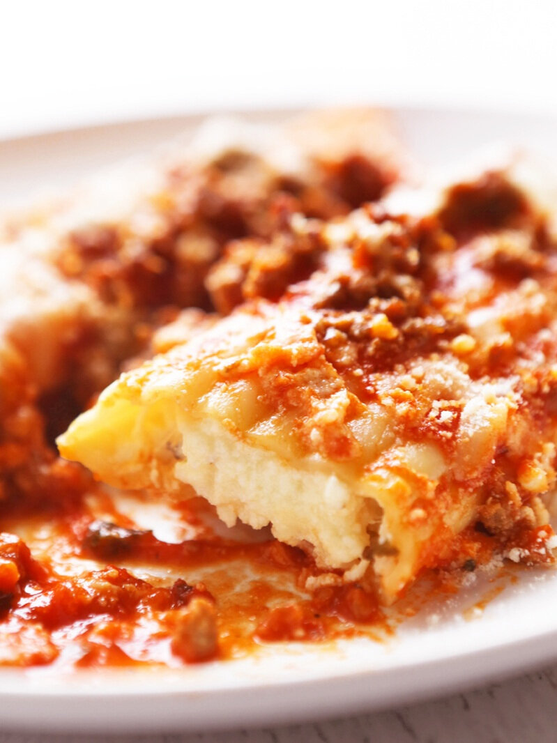 close up of piece of cheesy manicotti on plate surrounded by sauce