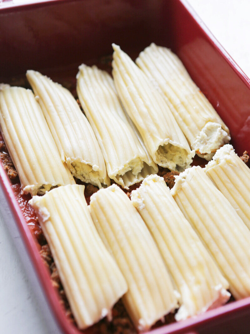 stuffed manicotti lined up in baking dish