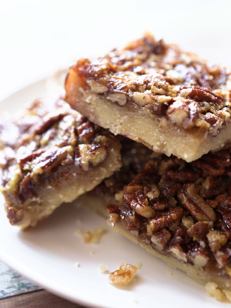 pecan pie bars stacked on a white serving plate