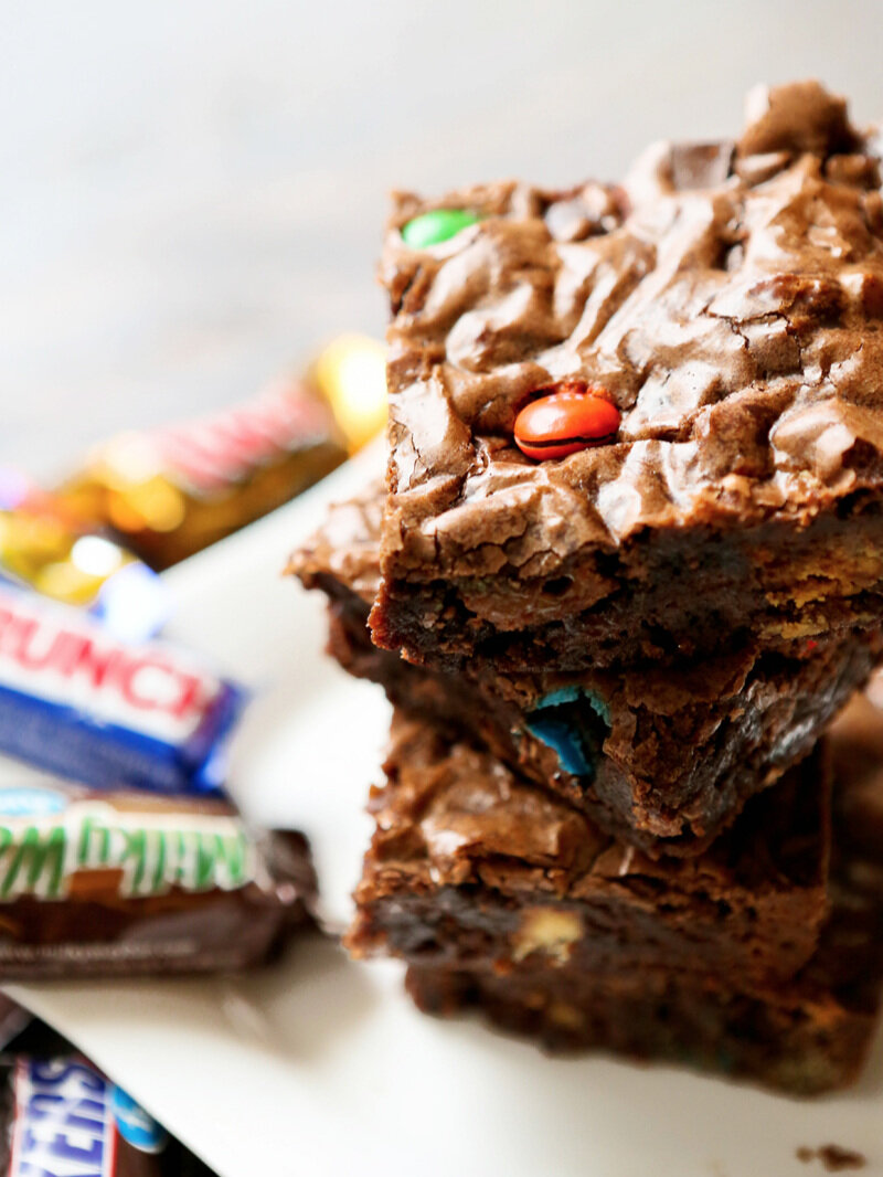 stack of candy bar brownies with fun size candy bars in background