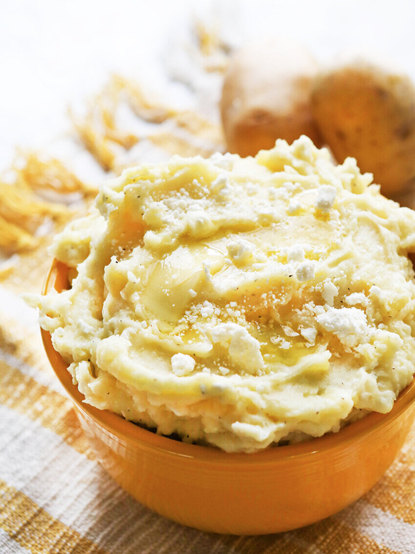 Heaping bowl of mashed potatoes with butter dripping down