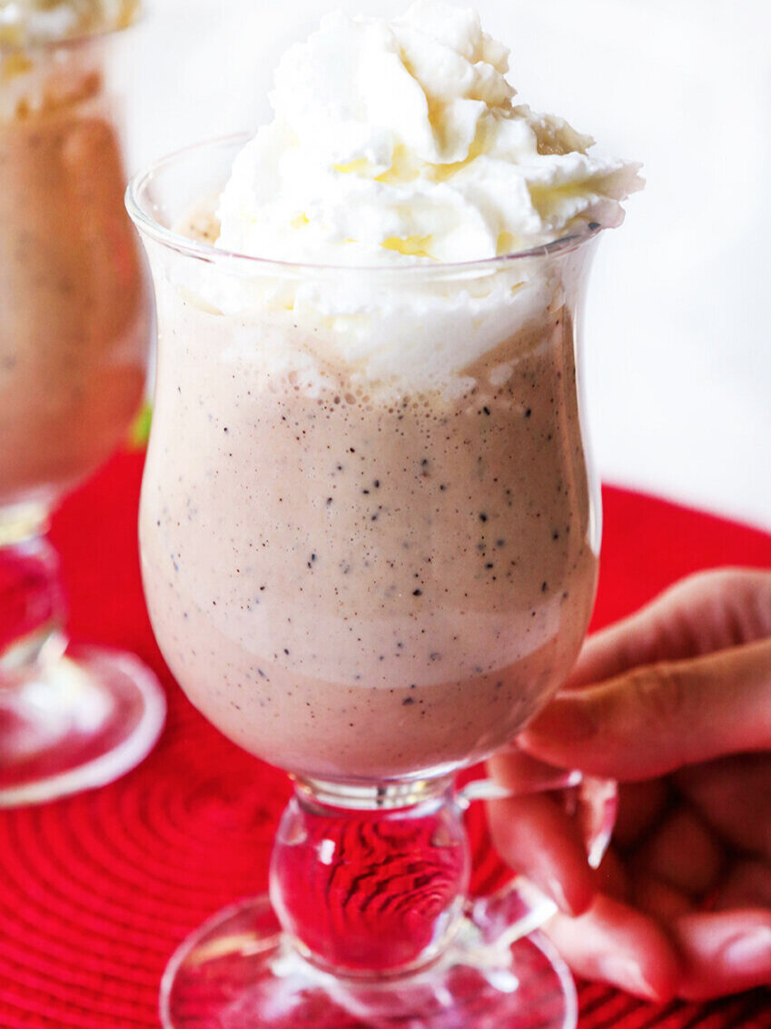 Hand holding handle of a glass of homemade baileys irish cream recipe with whipped cream