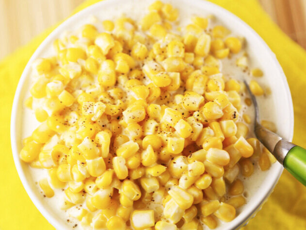 top view of bowl of creamed corn with a serving spoon inside
