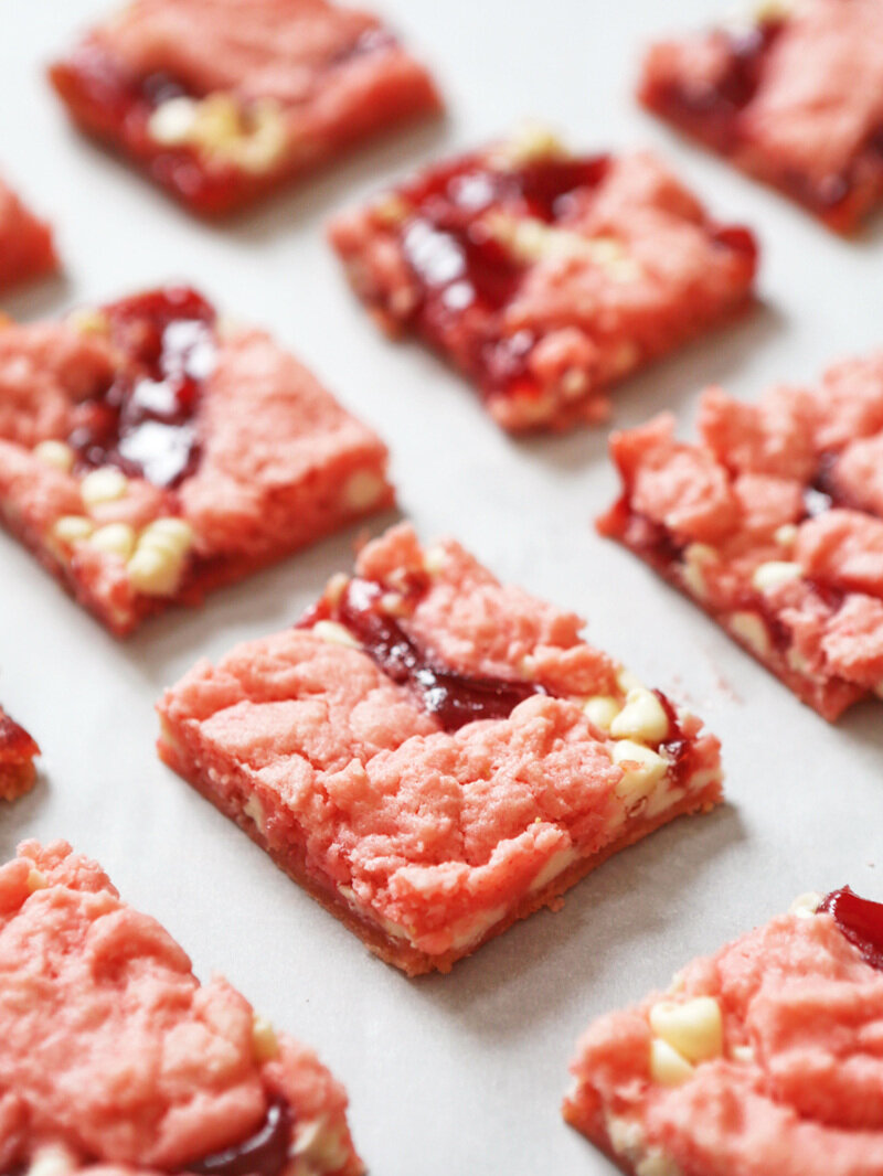 Strawberry brownies in a single layer on a piece of parchment