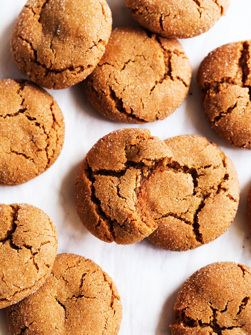 top view of molasses cookies on parchment paper, one with a bite taken out