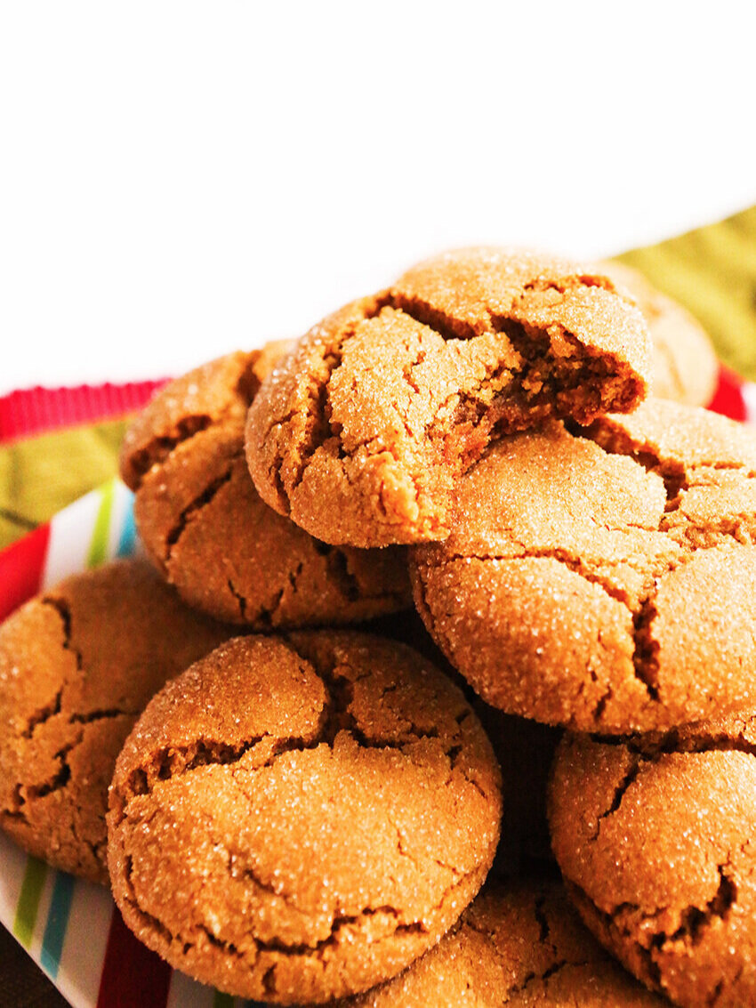 Stack of molasses cookies with a bite taken out of the top one