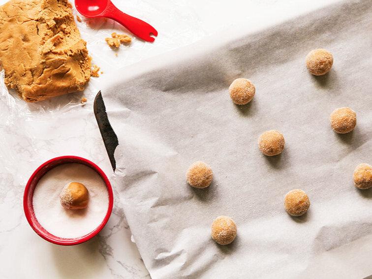 dough balls rolled in sugar on baking sheet sitting next to dough