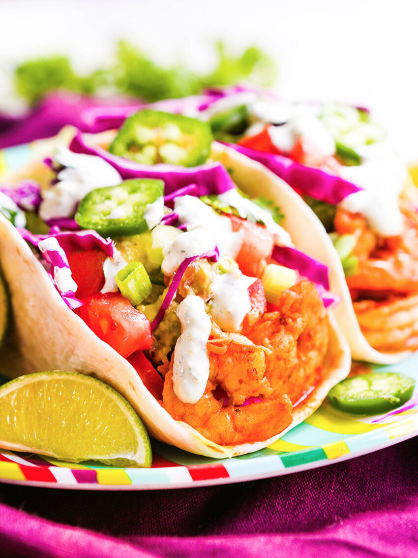 Shrimp tacos on a colorful plate loaded with toppings