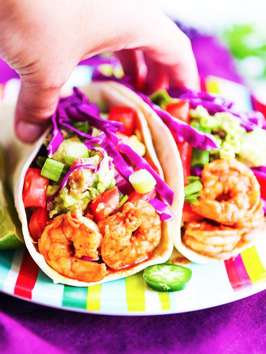 Hand grabbing two shrimp tacos at once