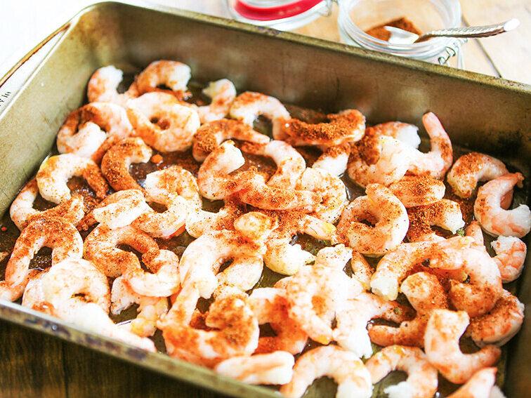 shrimp in baking pan with seasonings sprinkled over tops