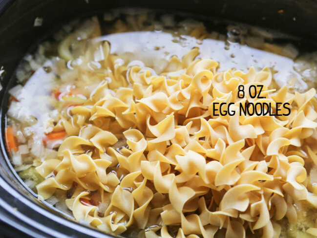 egg noodles on top of chicken noodle soup in crockpot