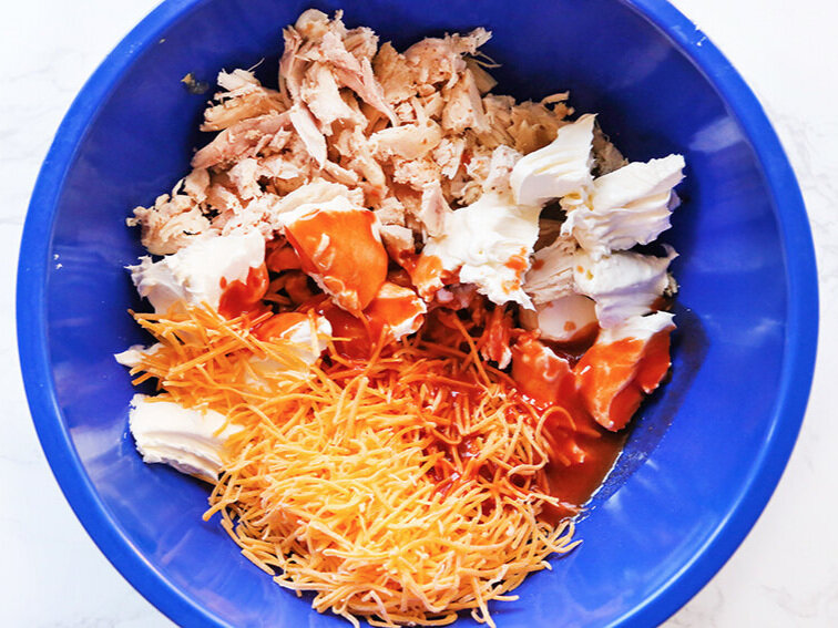 Buffalo chicken dip ingredients in mixing bowl