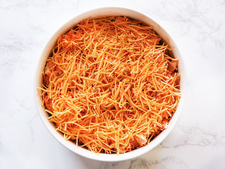 Shredded cheddar over top of easy buffalo chicken dip ready to be baked