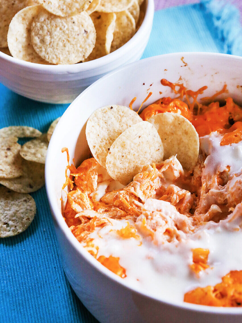 Pan of hot cheesy dip with tortilla chips next to bowl