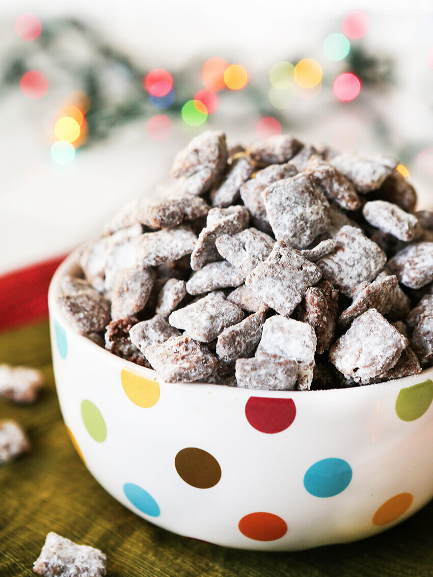 Heaping bowl of puppy chow with christmas lights in background