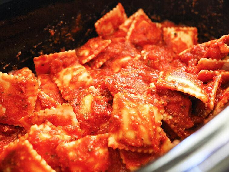 Ravioli in sauce sitting inside crockpot